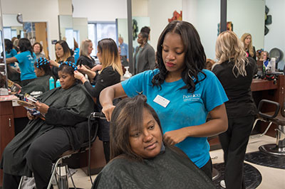 Students practice hair cutting on volunteers